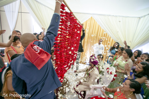 Indian wedding guests throwing rose petals at ceremony.