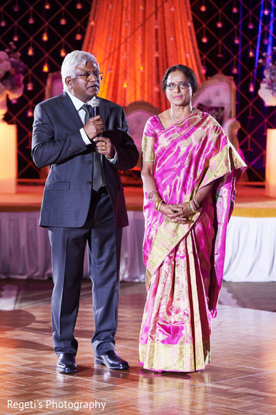 Indian parents at reception speech moment.