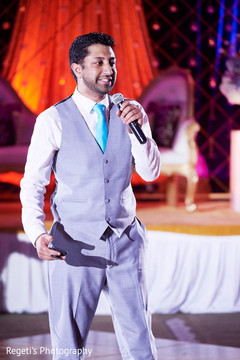 Indian groomsmen at reception speech moment.