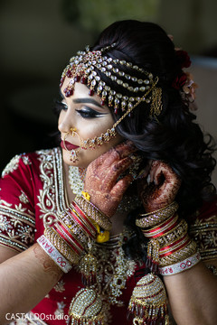 Lovely Indian bride putting her earrings on.