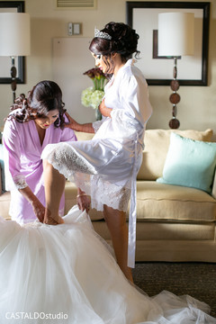 Indian bride putting her white dress on.