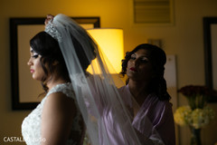 Indian bridesmaid putting bride her veil.