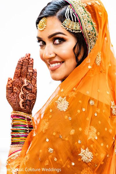 Dazzling bride showing her mehndi design