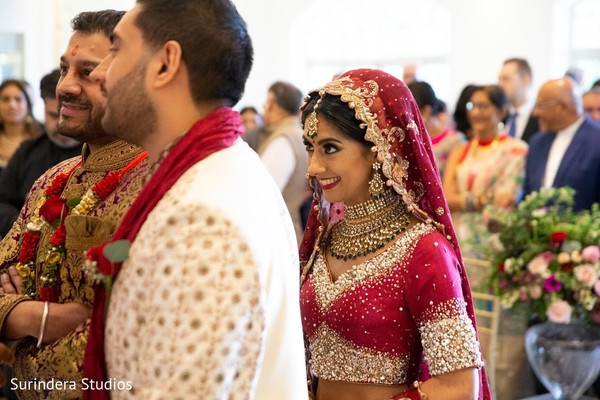 Indian bride being given to groom at the ceremony mandap.