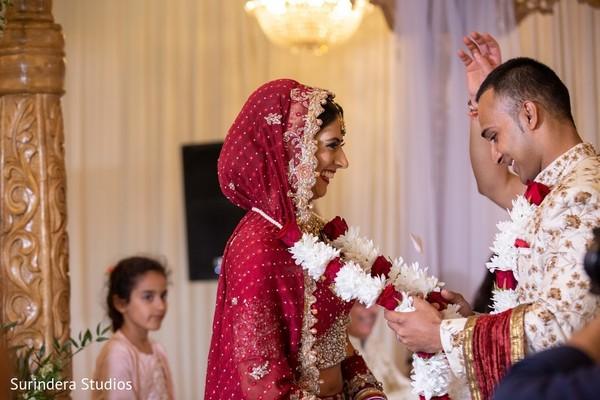 Indian groom putting garland to bride at jaimala ritual.