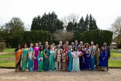Lovely Indian couple posing with bridesmaids and groomsmen.