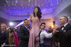 Indian bride being lifted up during reception.
