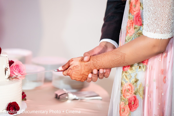 Mehndi design on display as the bride cuts the cake