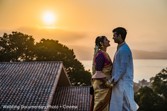 Indian bride and groom posing by the sun