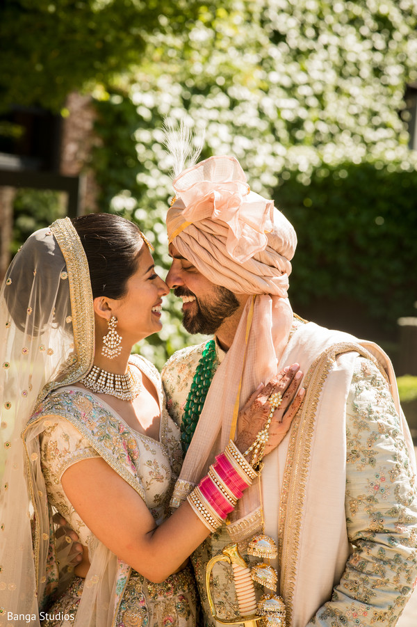 Indian couple posing outdoors on their ceremony outfits.