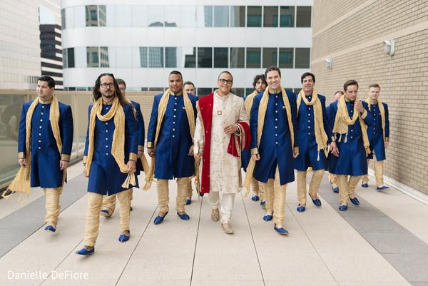 Elegant Indian groom with groomsmen outdoors.