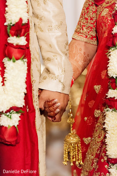 Closeup capture of Indian couple's hands at ceremony.