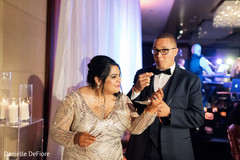Indian bride giving cake to groom.