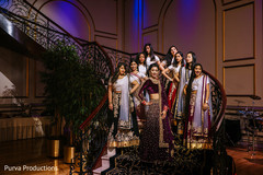 Indian bride and bridesmaids posing on the stairs.