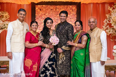 Indian couple with parents posing for photo shoot.