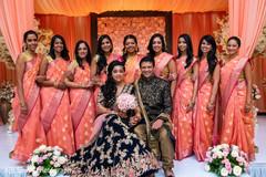 Glamorous Indian couple posing with bridesmaids.
