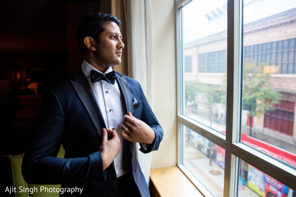 Lovely Indian  groom looking out the window.