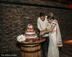 Indian wedding cutting cake moment capture.