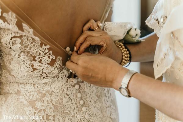 Maharani getting help to button her wedding dress.