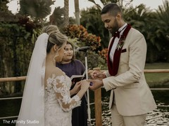 Indian groom putting wedding ring to bride.