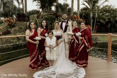 Indian bride and groom posing with bridesmaids and flower girl.