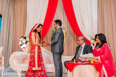 Indian bride putting the wedding ring to groom.