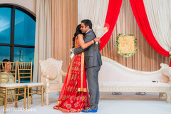 Sweet capture of Indian couple hug at ceremony.