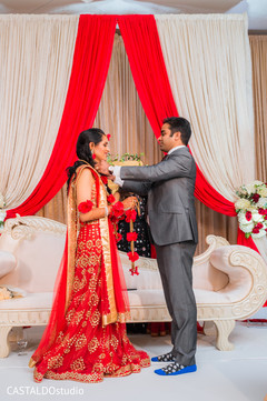 Indian groom putting the red garland to bride.
