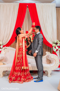 Indian bride putting the red garland to groom.