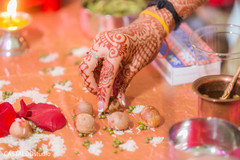Indian bride grabbing a nut at ceremony ritual.