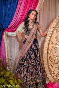 Glamorous indian bride posing on her sangeet lehenga.