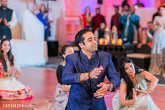 Indian groom dancing with bridesmaids at sangeet.