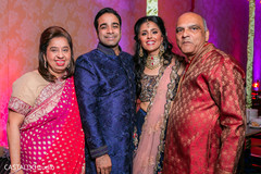 Joyful Indian couple posing with guests.