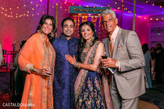 Charming Indian couple with sangeet guests capture.