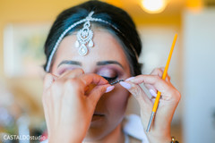 Indian bridal getting her makeup done.