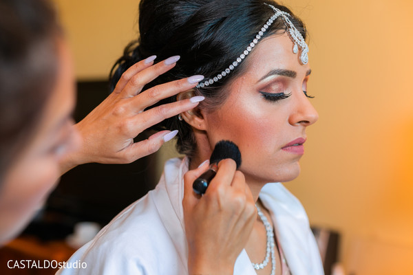 Indian bride getting the last touch ups of makeup.