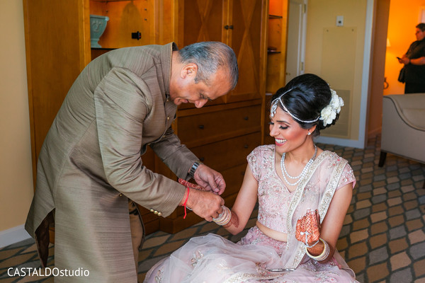 Indian bride's father putting an bracelete to bride.
