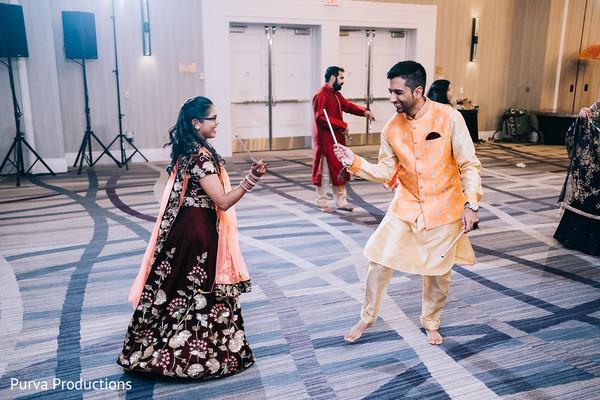 Indian couple using dandiya raas sticks at sangeet dance.