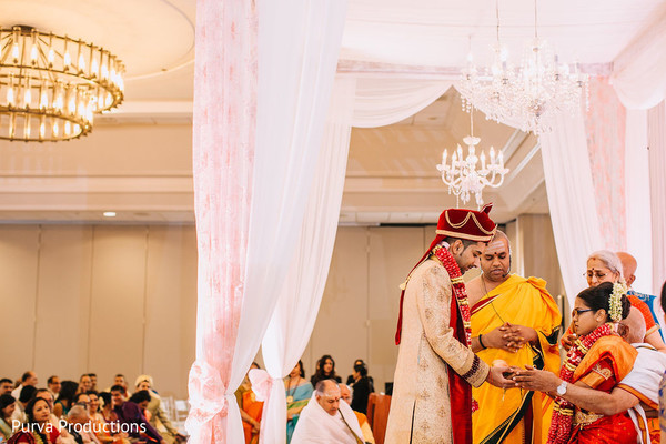 Indian groom giving bride the coconut at ceremony.