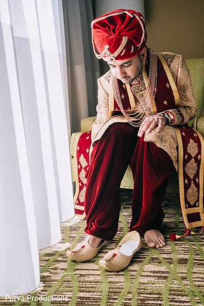 Charming indian groom getting his shoes on.