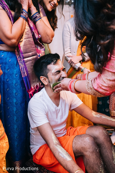 Fun capture of Indian groom being smeared with turmeric paste.