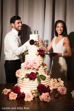 Indian bride and groom sharing a slice of cake