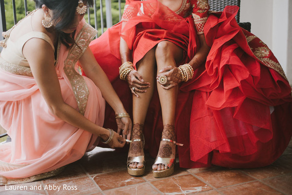 Indian bride being assisted by bridesmaids