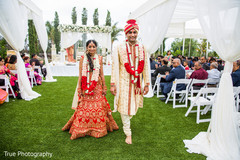 Indian bride and groom walking out from the ceremony isle.