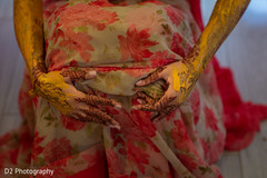 Indian bride with turmeric past on her hands.