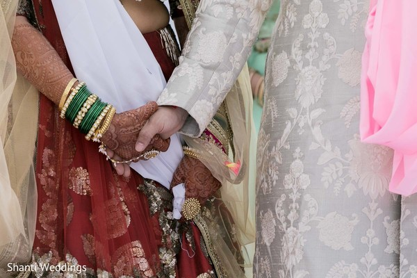 Indian bride holding Raja's hand