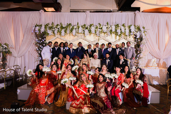 Indian groom and bride posing with guests
