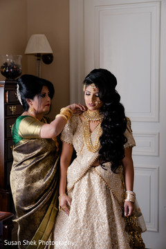 Indian bridal putting her kundan on.