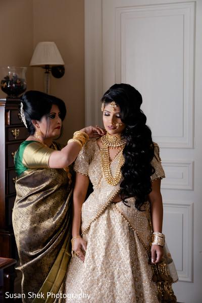 Indian bridal putting her kundan on.