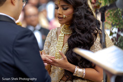 Indian bride putting ring to groom at ceremony.